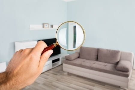 Person Inspecting Home with Magnifying Glass